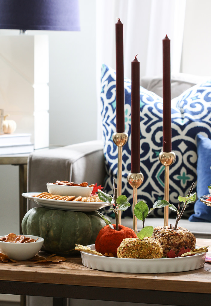 candied apples in a dish, crackers on a plate with decorative squash pumpkin on a table with a sofa and pillows in the background