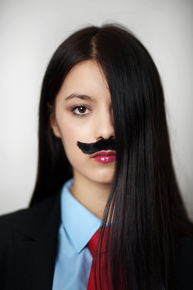 portrait of a young woman dressed up in a man's suit and tie wearing a fake mustache